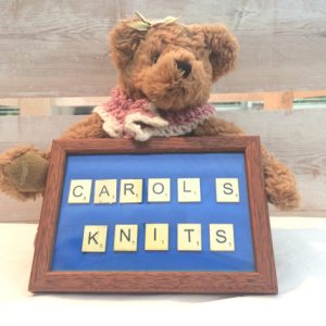 teddy bear holding a sign for Carol's knitting